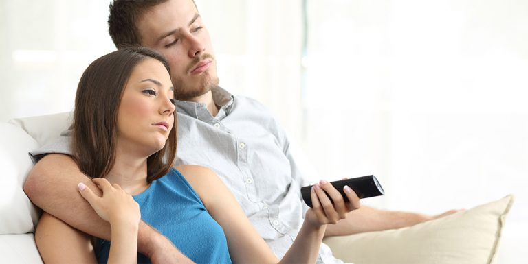 Couple on a couch with remote
